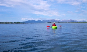 Kayaking Roundstone aby with 12 bens backdrop Galway Ireland for CWE website